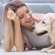 Blonde junge Frau kuschelt mit Retriever