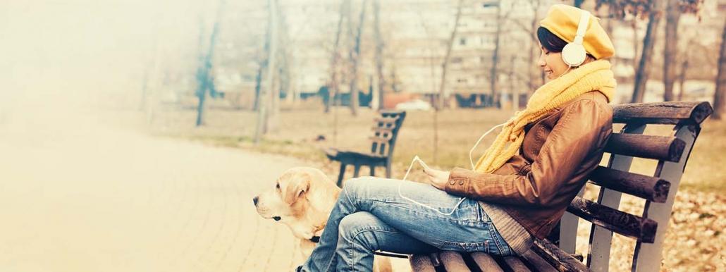 Mein Herz bellt - Frau mit Kopfhörern draußen auf einer Bank mit Hund