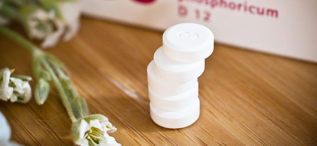 Schüßlersalze in Tablettenform neben Kräutern und Verpackung